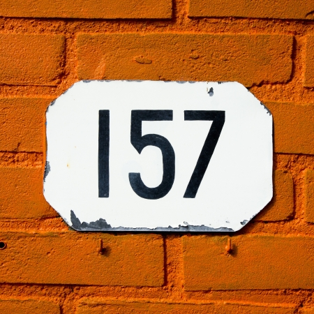 house number hundred and fifty-seven on an orange painted brick wall photo