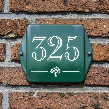enameled: enameled house number three hundred and twenty-five atop a small tree symbol  White lettering on a green plate Stock Photo