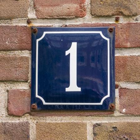 number one: número de casa esmaltado uno. Letras blancas sobre un fondo azul