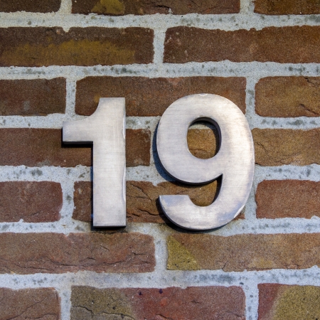 three dimensional metal house number nineteen on a brick wall Stock Photo