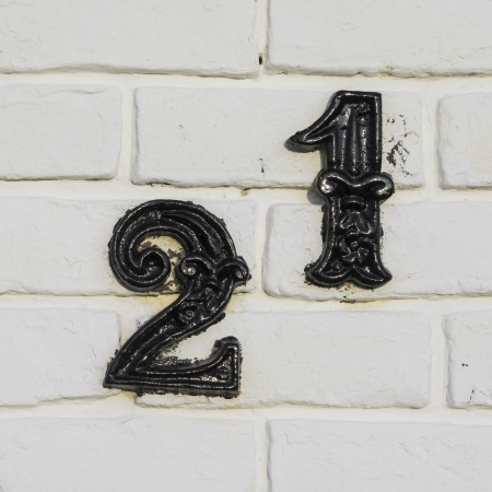 cast metal house number twenty-one. Separate black lettering on a white  painted brick wall. Stock Photo