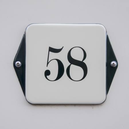 enameled: enameled house number fifty-eight. Black lettering on a white background. Stock Photo