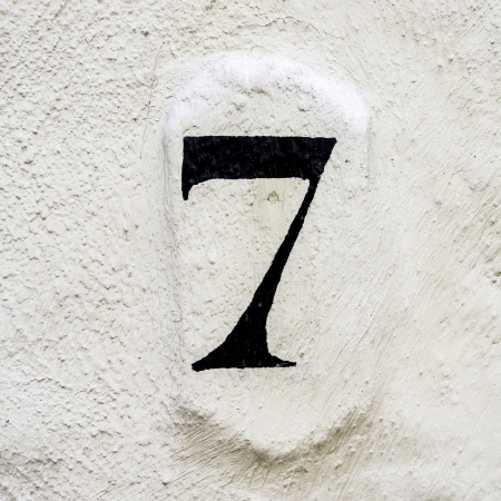 house number seven painted on a white plastered wall photo