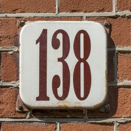 enameled: enameled house number one hundred and thirty-eight. Brown lettering on a white background. Stock Photo