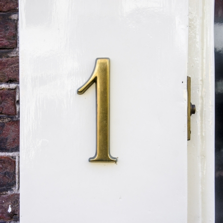 1 object: cast bronze house number one next to a door bell