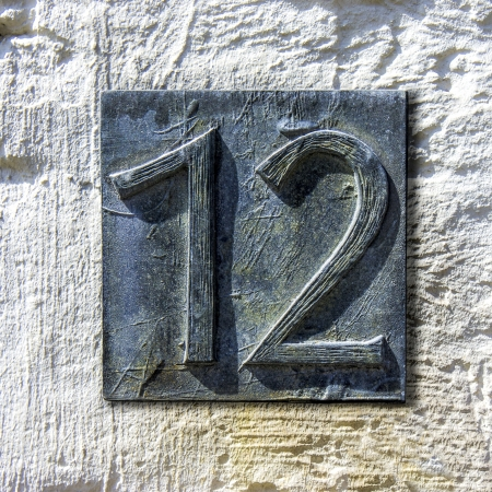 cast metal type: Bronze cast house number twelve on a plastered wall Stock Photo