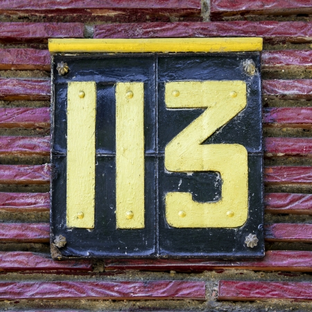 cast metal type: house number one hundred and thirteen, on a cast metal plate