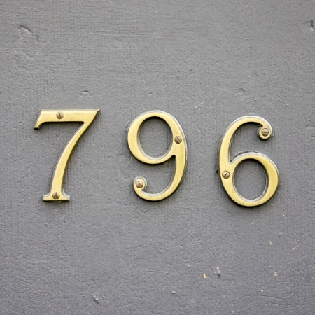 cast metal type: cast bronze house number seven hundred and ninety-six on a gray wall
