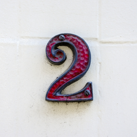 two objects: red decorated house number two on a white wall