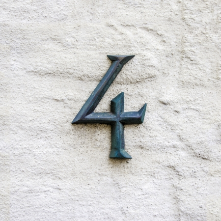 cast metal type: cast bronze house number four on a white plastered wall