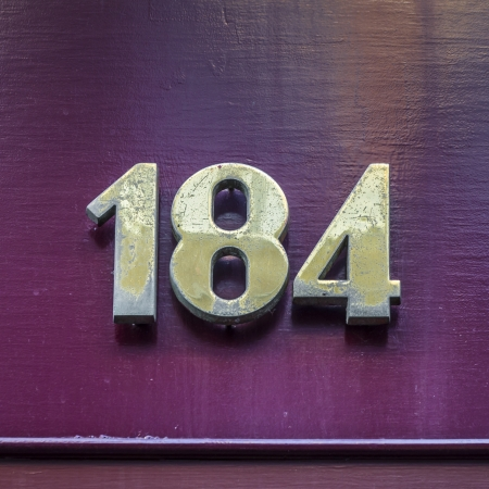 lacquered: House number one hundred and eighty-four  Bronze colored lettering on a lacquered purple background Stock Photo