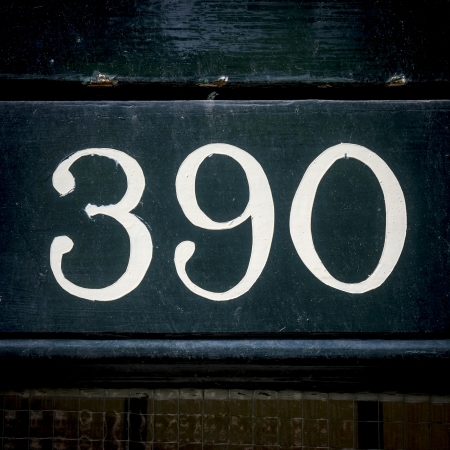 lacquered: House number three hundred and ninety  White lettering painted on lacquered wood