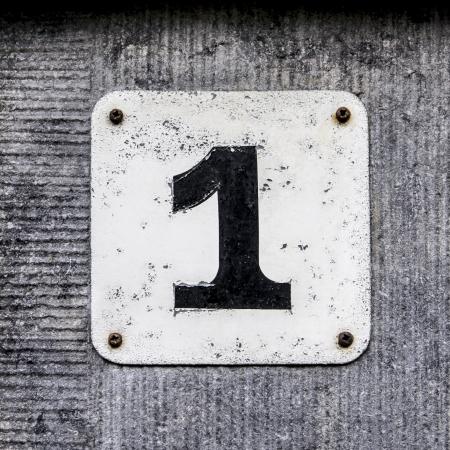 number one: Número de casa: uno letras Negro en un plato blanco