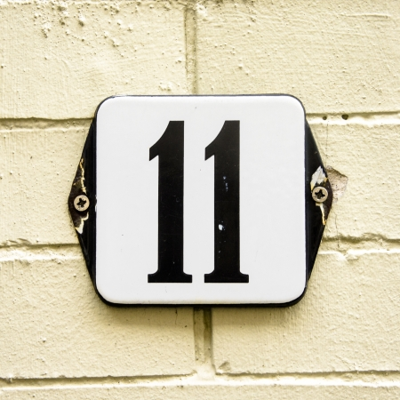 Enameled house number eleven on a yellowish brick wall photo
