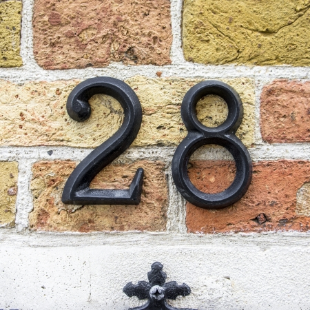 cast metal type: Cast metal house number twenty eight on a brick wall