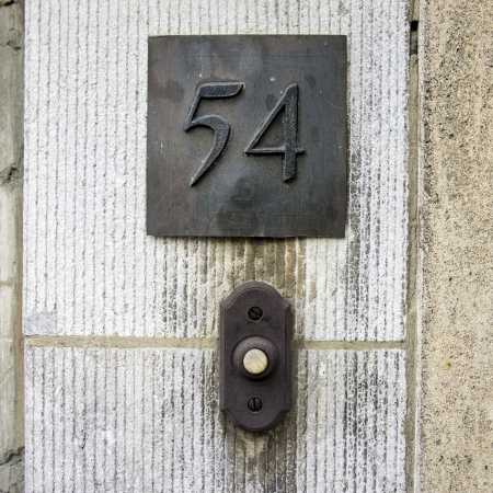 cast metal type: bronze house number fifty four above a doorbell.
