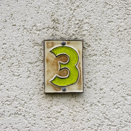 plastered: Ceramic house number three on a plastered wall Stock Photo