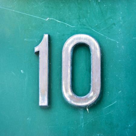 numero diez: casa n�mero diez de metal sobre un fondo verde.