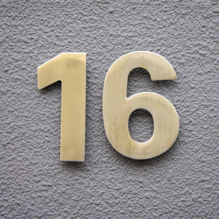 number 16: Brass house number sixteen on a plastered wall. Stock Photo