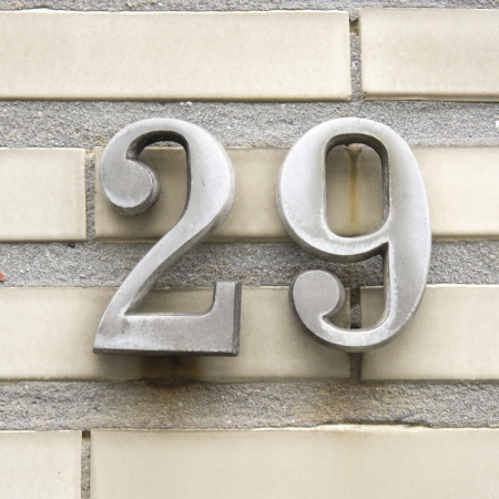 cast metal type: metal house number twenty nine on a wall of white bricks Stock Photo
