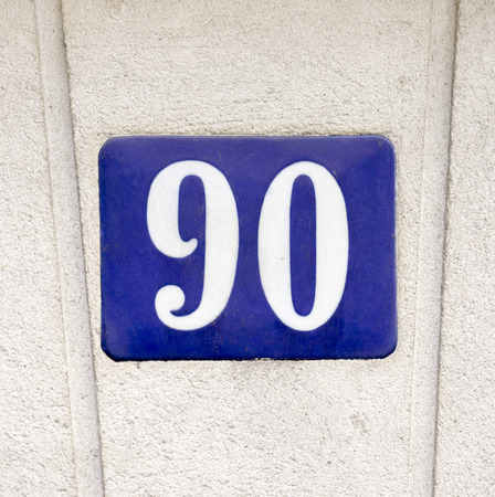 porcelain house number ninety. White lettering on a blue background. Stock Photo
