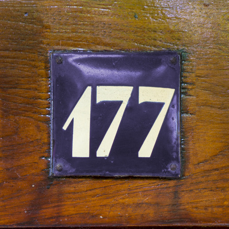 enameled: house number one hundred and seventy seven. White lettering on a purple enameled plate attached to a wooden panel.