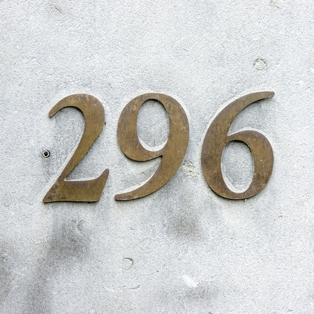 cast metal type: Bronze house number two hundred and ninety six on a concrete wall.
