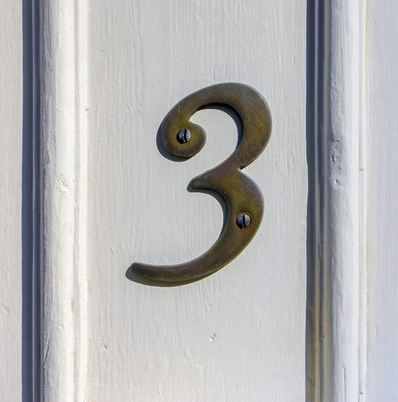 cast metal type: Bronze house number three attached to a wooden panel.