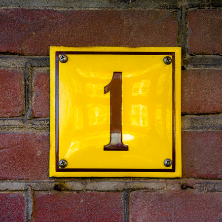 enameled: Enameled house number one. Brown lettering on a yellow background. Stock Photo