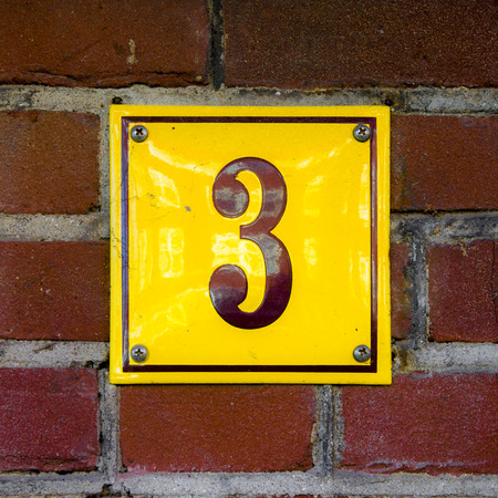 enameled: Enameled house number three. Brown lettering on a yellow background.