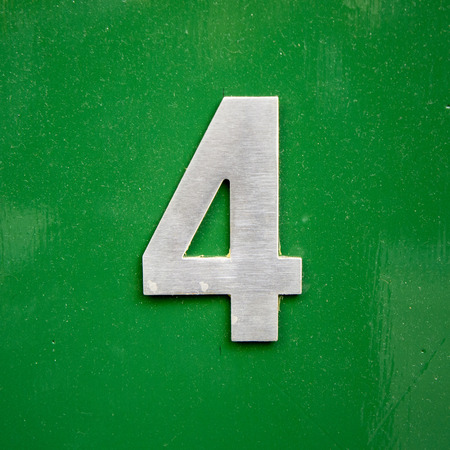 lacquered: metal house number four on a green lacquered panel