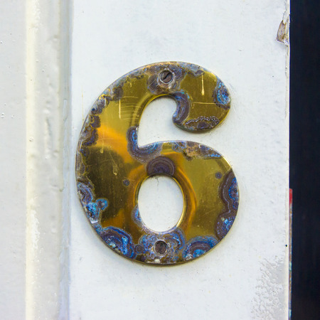 affected: Brass house number six heavily affected by the weather Stock Photo
