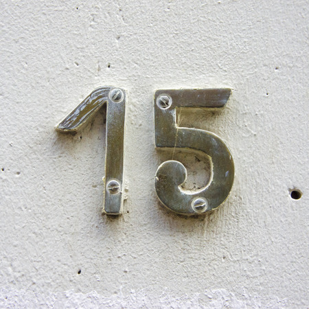 bronze house number 15 on a white plastered wall
