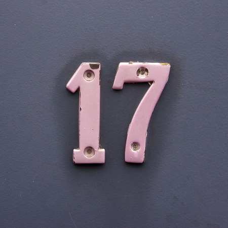house number seventeen. Pink painted brass numerals.