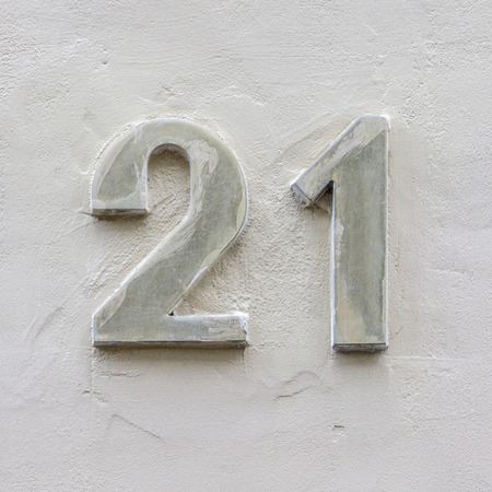 twenty one: metal house number twenty one on a white plastered wall