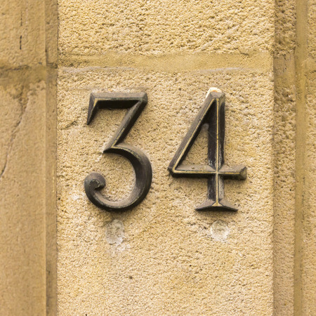cast metal type: house number thirty four. Cast bronze numerals on a stone wall