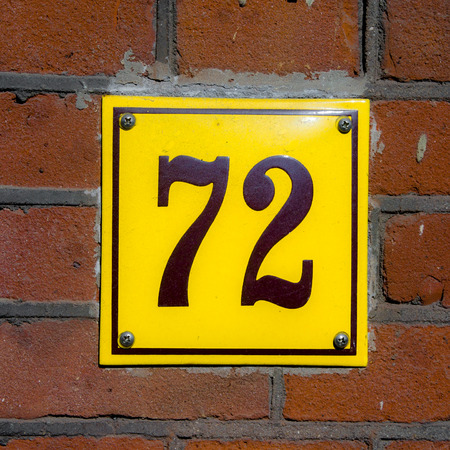 seventy two: Enameled house number seventy two. Brown lettering on a yellow background.