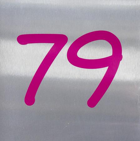 pink house number seventy nine on a brushed metal background. photo