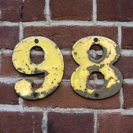affected: affected brass house number ninety eight on a brick wall.