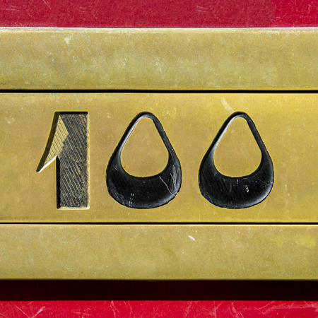 cast metal type: house number one hundred engraved in a bronze plate. Stock Photo
