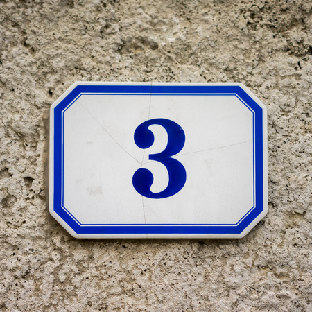 blue house number three on a ceramic tile photo