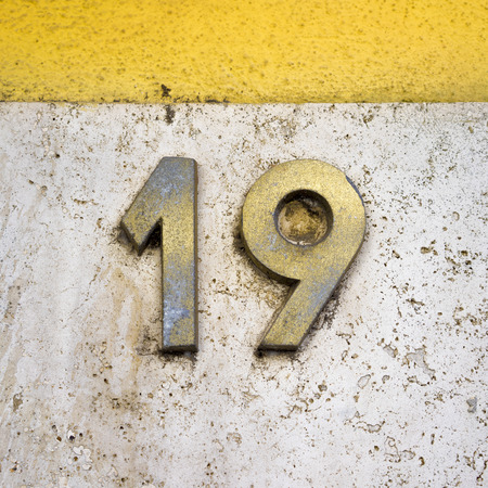 nineteen: brass house number nineteen on a marble wall
