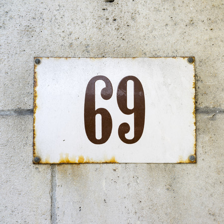 enameled: enameled house number on a wall of natural stone