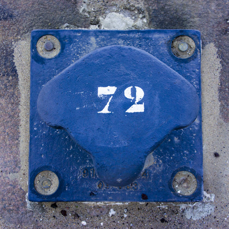 seventy two: number seventy two on a blue painted metal bollard.