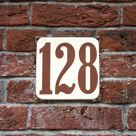 enameled: enameled house number on a red brick wall