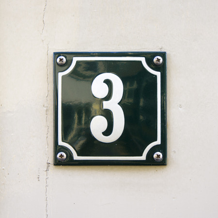 enameled: Enameled house number three. White numerals on a green background.
