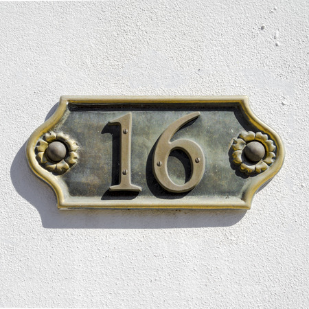 cast metal type: cast bronze house number sixteen on a white stucco wall Stock Photo