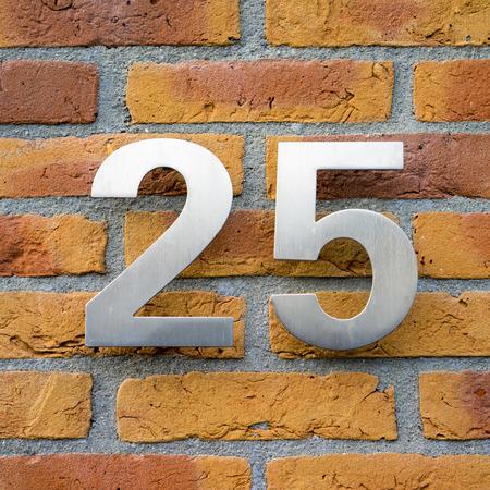 ladrillo: la casa del metal n�mero veinte p�fano en una pared de ladrillo