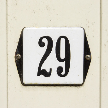 enameled house number twenty nine. Black numerals on a white background Stock Photo