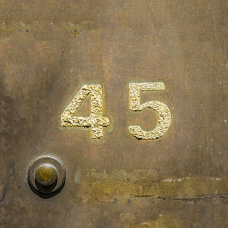 door bell: House number forty five on a copper plate next to  a door bell.